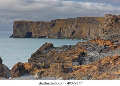 Black sand beach with Lundadrangur Rock Arch in Dyrholaey, South Coast, Iceland