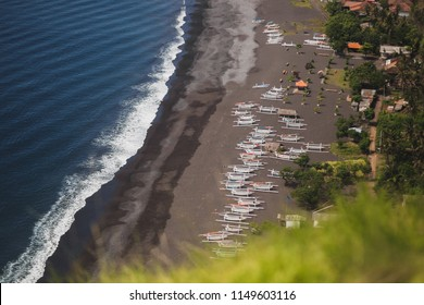 Black sand beach with a lot of traditional balinese boats, view from cliff in Candidasa