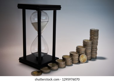 Black sand clock with white sand behind growing staples of coins and a two euro coin leaning against them