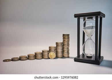Black sand clock with white sand beside growing staples of coins and a two euro coin leaning against them
