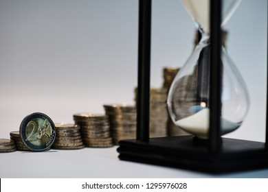 Black sand clock with white sand in the foreground and growing staples of coins blurred in the background with a two euro coin leaning against them