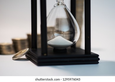 Black sand clock with white sand and a two euro coin leaning against it in the foreground with growing staples of coins blurred in the background