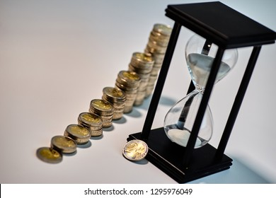 Black sand clock with white sand and a two euro coin leaning against it with growing staples of coins beside it