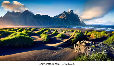 Black sand dunes on the Stokksnes headland on southeastern Icelandic coast with Vestrahorn (Batman Mountain). Colorful summer morning Iceland, Europe. Artistic style post processed photo.