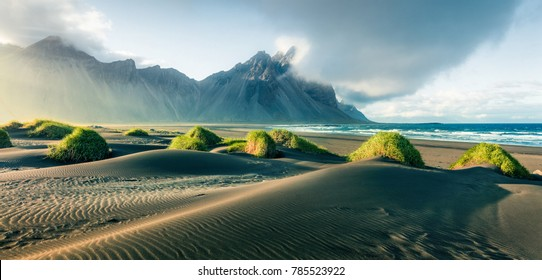 Black sand dunes on the Stokksnes headland on southeastern Icelandic coast with Vestrahorn (Batman Mountain). Picturesque summer panorama of Iceland, Europe. Instagram filter toned.