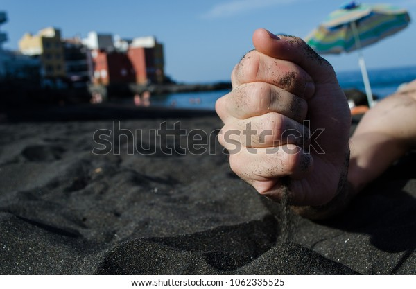 Black sand is pouring from the hand of the man on the beach in Canary Islands. Close up of the black volcanic sand.