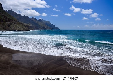 Black sand volcanic beach and view of Anaga mountains on northern coast in fishing village of Taganana, Tenerife island, Spain