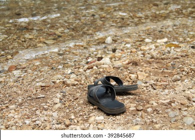 Black sandals are put down on riverside