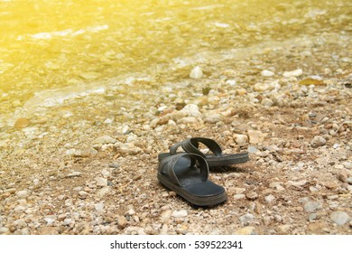 Black sandals are put down on riverside. Artificial light was added on the top left corner for warm tone style.