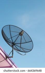 Black satellite dish antennas on blue sky.