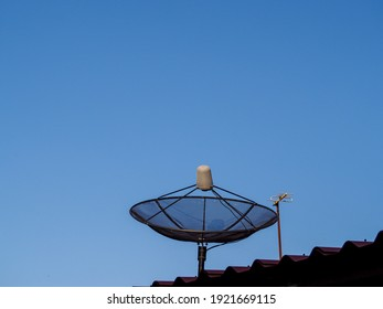 Black satellite dish on the roof in the sunlight, has space