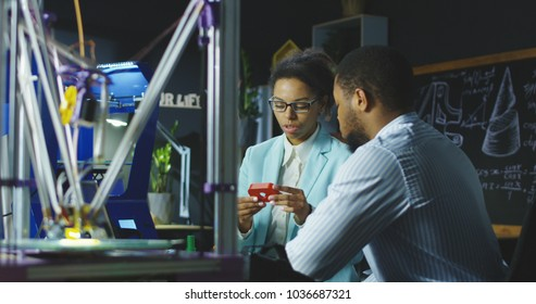 Black scientists sitting in modern laboratory and talking about new technologies.