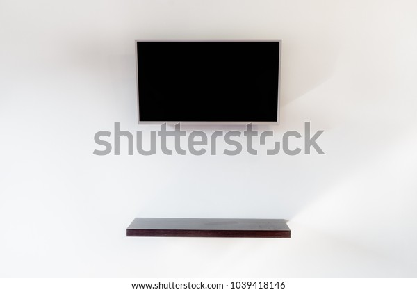 Black screen smart tv with dark brown wooden shelf hanging on gray wall background in living room interior design.