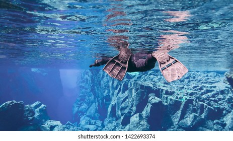 Black scuba diving snorkeling fins in crystal clear blue glacier transparent water colorful cliff rocks around in the national park Thingvellir Silfra fissure drift crack between two tectonic plates