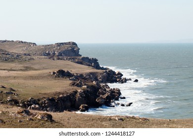 Black Sea ancient coast where the sea meets the weathered and smoothed mountains, rotted rocks, eroded stratum, sea-shore terrace. Dry steppes etched by cattle and sheep