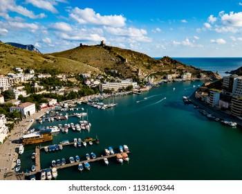 Black Sea bay and marina from aerial view. Coastal town. Yacht club. Balaklava, Crimean peninsula