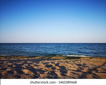 The black sea beach (Romania) at sunset. A lone swimmer is heading far into the sea.