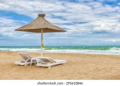 Black Sea beach with umbrellas, fine sand, cool water and blue cloudy sky.