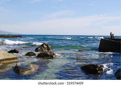 Black sea coast of Crimea,  view clear water,stones and 'Alyosha' - vintage sculpture of man looketh upon sea on Foros pier