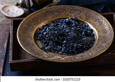Black sea salt in a brass plate on a rustic wooden box on wooden background. Selective focus