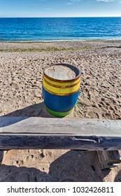 Black Sea  shore with a colored barrel and a massive wooden bench