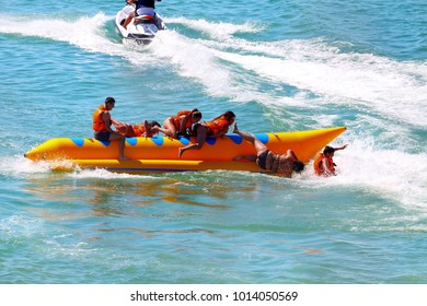 BLACK SEA, UKRAINE - JULY 31, 2017: Inflatable banana boat with tourists in blue calm sea. Group of people riding banana boat. People flip over from banana boat