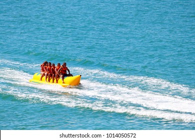 BLACK SEA, UKRAINE - JULY 31, 2017: Inflatable banana boat with tourists in blue calm sea. Group of people riding banana boat. Speeding away.