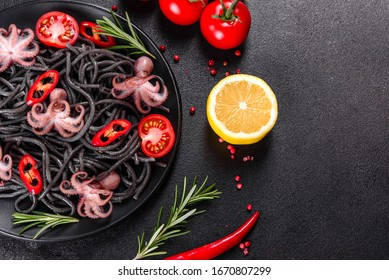 Black seafood pasta with shrimp, octopus and mussels on black background. Mediterranean gourmet food. Black pasta with octopus on a black stone plate