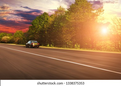 A black sedan car driving fast on the countryside asphalt road with green trees against night sky with sunset
