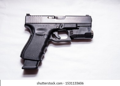 A black semi automatic 9mm pistol with an attached flashlight under the muzzle and an extended magazine out of the grip of the gun on a white background
