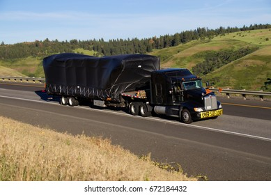 Black Semi pulling an oversize load on a flatbed trailer. June 20th, 2017 Oregon, USA
