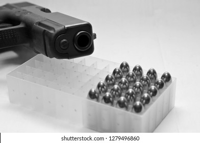 A black semiautomatic 9mm pistol laying on top of a plastic bullet case filled with twenty gold, full metal jacket bullets in black and white