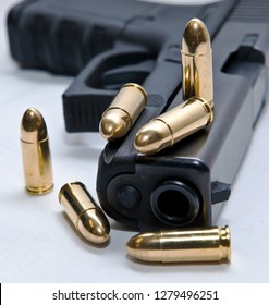 A black semiautomatic 9mm pistol with six gold, full metal jacket bullets on it and in front of it with a white background