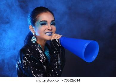 Black Sequin Jacket on Blue Fashion Make Up Asian Beautiful Models black hair holding plastic megaphone yelling, studio lighting dark background smoke copy space