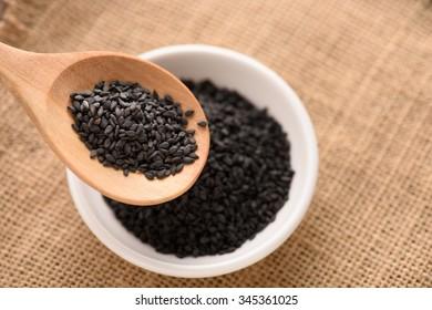 black Sesame close up shot in wood spoon  on sack background