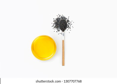Black sesame oil and sesame seeds on spoon isolated on white background. Flat lay. Top view