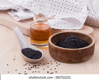 Black sesame oil and sesame seeds set up on wooden table
