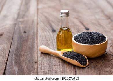 Black sesame seeds in wooden bowl and spoon and sesame oil in glass bottle isolated on wooden table background. Copy space.