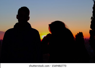 black shadow of a couple in the sunset