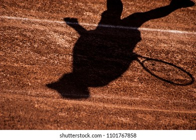 Black shadow of tennis player on tred clay ennis court