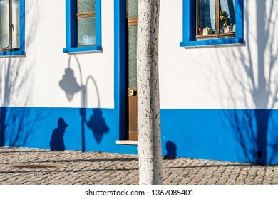 Black shadows of people, tree and lantern on traditional fisherman's house in Tavira, Algarve, Portugal