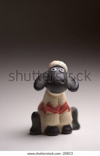 A black sheep wearing a wooly sweater and hat.