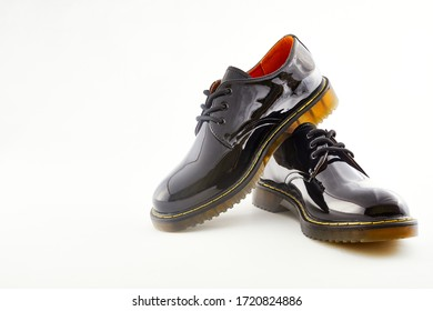 Black shiny leather shoes for woman. Female fashion footwear on white background. Formal trendy oxford boots.