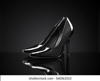 Black shiny stiletto heeled pumps on black reflective background.