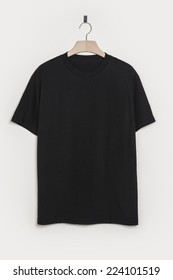 A black shirt front side with wooden hanger isolated white.