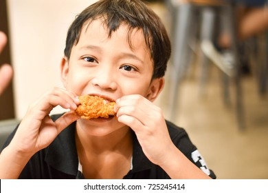 The black shirt young Asian boy enjoys eating the crispy fried chicken in the shop.