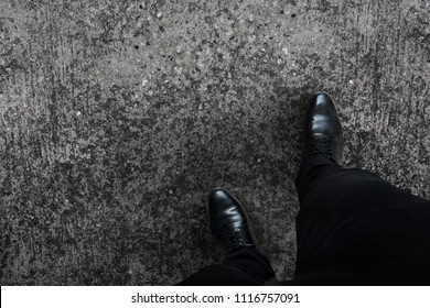 Black shoes business man stepping his right foot walking top view.