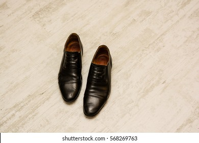 Black shoes are on the floor in office