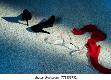 Black shoes, red scarf and cocktail glass in lipstick dropped on white carpet.