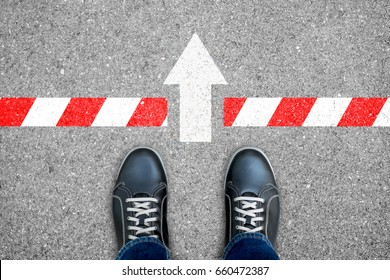Black shoes standing at the limit but direction sign push through the dead end line representing way out exit.